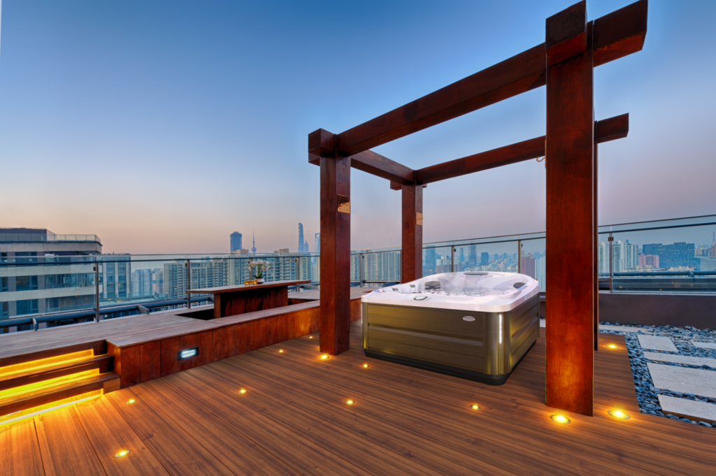 Jacuzzi Hot Tub installed under a pergola on a rooftop, with a beautiful view of the city.